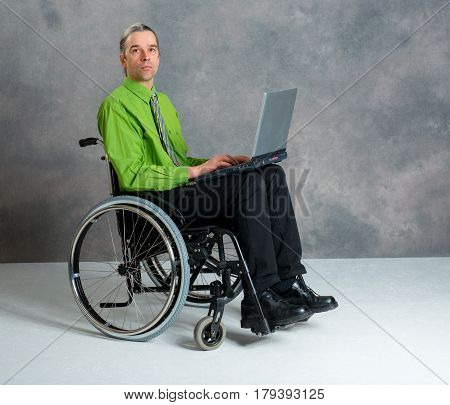 Disabled Business Man In Wheelchair With Computer
