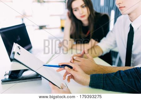Just put your signature here. Confident young man in shirt and tie holding some document and pointing it while sitting together with cheerful young couple at the desk in office