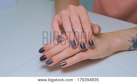 Woman shows her new manicure. Purple nail. Beauty and nail care concept