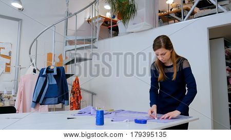 Professional dressmaker, designer measuring cloth for sewing at atelier. Fashion and tailoring concept