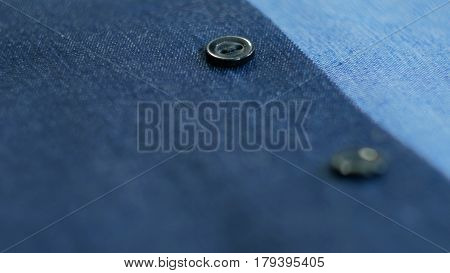 Close up view of smart business women's suit jacket - denim, texture, buttons. Selective focus with shallow depth of field