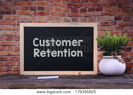 Customer Retention word on blackboard with green plant
