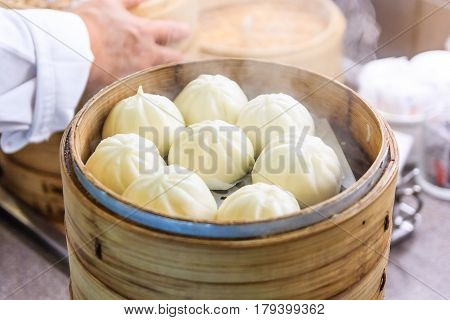 Steamed pork buns (chinese dim sum) in bamboo basket in a restaurant.