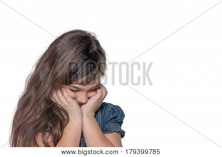 Portrait of ashamed brunette long haired little girl isolated on the white background. The girl is holding her face by both hands.