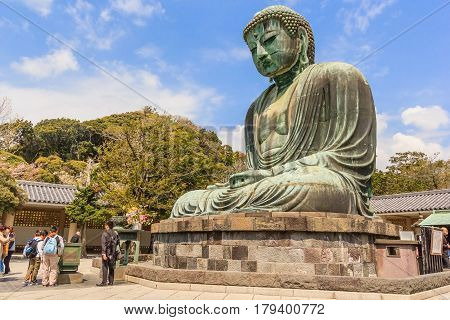 KAMAKURA JAPAN - APRIL 14 2014: Scenery of the Great Amida Buddha and tourists in Kamakura. Kamakura Daibutsu is the famous landmark located at the Kotoku-in temple in Kanagawa Prefecture.