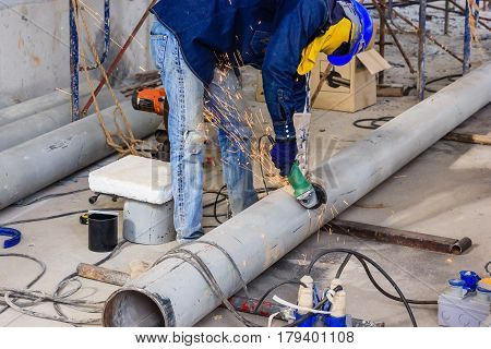 Heavy industry worker cutting steel pipe with wear protective mask by power saw in construction site.
