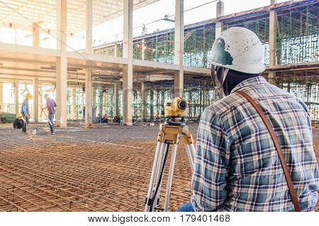 Surveyor worker make measuring with theodolite equipment at factory construction site.