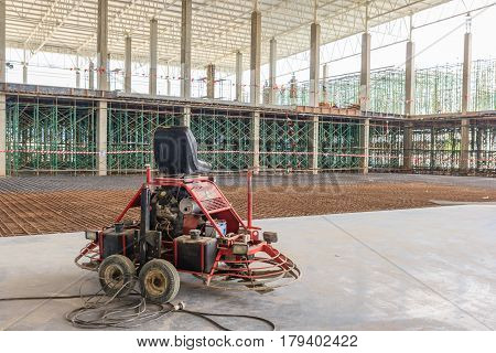 Double power trowel finishing concrete floor at construction building site smooth concrete surface.