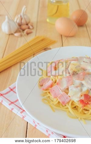 Spaghetti carbonara with chopped bacon cheese sauce and checkered towel on white dish over wooden table background Italian food concept.