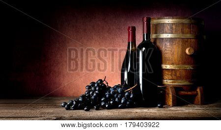 Bottles of wine with cask and grape