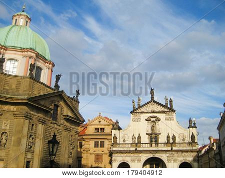 Clementinum Cathedral (St. Clement and St. Salvator Church) and square in Prague old town, Czech Republic. Historic complex of buildings famous landmark in downtown Prague city with empty blue sky background