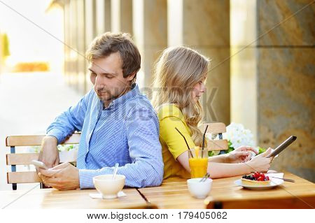 Young dating couple using smart phone and tablet pc in the outdoor cafe