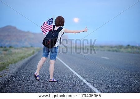 Young Female Tourist Hitchhiking Along A Desolate Road