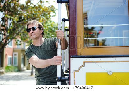 Male Tourist Taking A Ride In Famous Cable Car In San Francisco