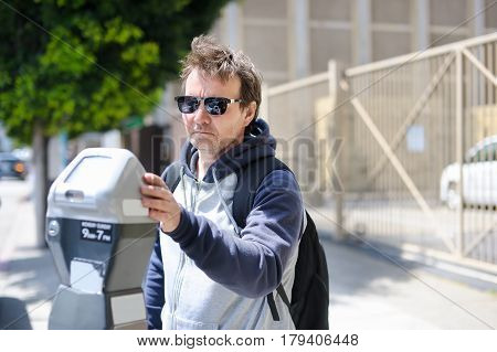 Man Using Street Parking Meter