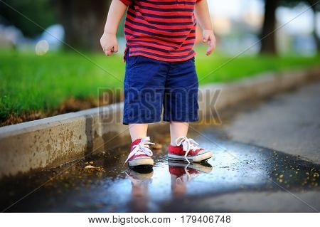 Toddler Boy Standing In A Puddle