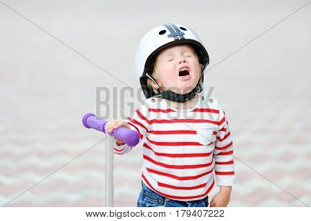 Crying Boy In Safety Helmet With Scooter