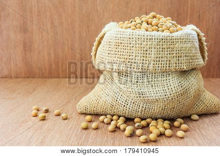 Soybean in hemp sack bag on a wooden table background Closed up