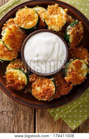 Delicious Slices Of Zucchini In Breadcrumbs With Sour Cream Close-up. Vertical Top View