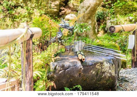 Dragon fountain and water dippers for Ritual Hand Washing before entering the temple in Japan culture