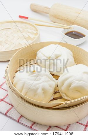 Steamed pork buns (chinese dim sum) in bamboo basket serve with chopsticks and napkin on a white background Closed up