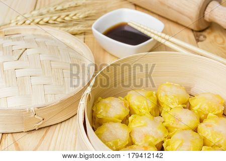 Steamed dumplings (chinese dim sum) in bamboo basket on wooden table background serve with chopsticks and napkin on wooden background. Closed up