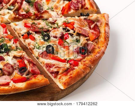 Close up view on piece of pizza with salami on wooden cutting board. Isolated on white with clipping path