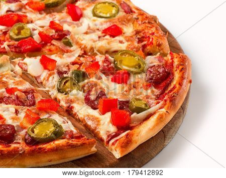 Close up view on piece of hot spicy pizza with pepperoni and hot pepper on wooden cutting board. Isolated on white with clipping path