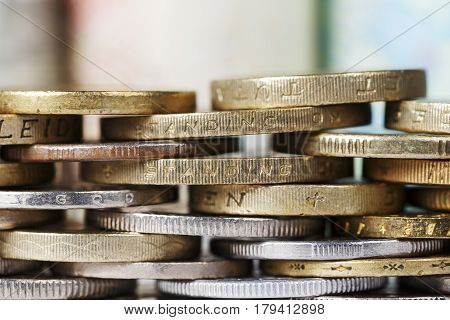 Several stacked various coins are the background