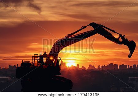 Excavator loader model with Silhouette on sunset at city building backgroundConcept Double exposure