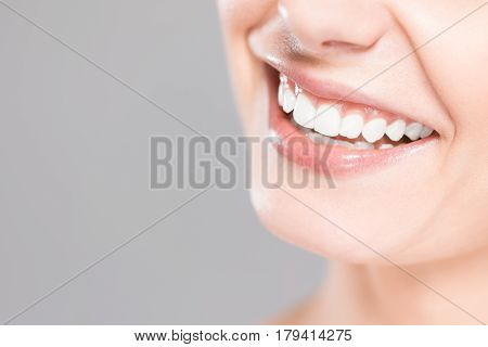 Beautiful smile young woman. White teeth on the master plan. Free space and background to use.
