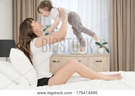 Young beautiful and smiling mother with baby girl. Daughter close to loving mom.