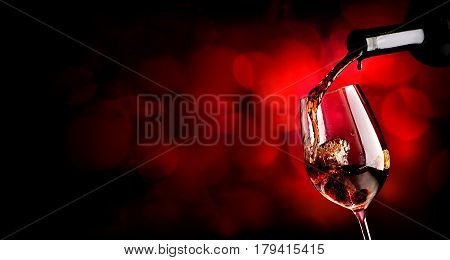 Wine pouring in wineglass on the vinous background