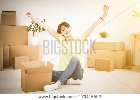 Young happy woman a student moved into a new apartment. Unpacks boxes in the new house. She raised her hands up as a sign of success.