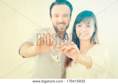 A young couple holding hands house key. The joy of a new apartment.