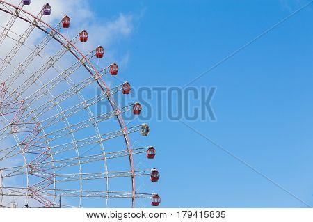 Festival funfair giant ferris wheel against blue sky background