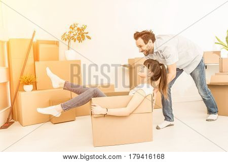 Young couple people have fun while moving to a new apartment. Boy pushes box with the girl. Happy people in the new house.
