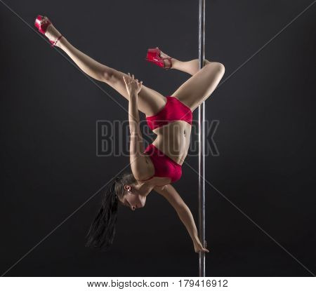 A young girl with long hair performs exercises on the pole in the red swimsuit. Studio shooting performances on the pole on a black background.