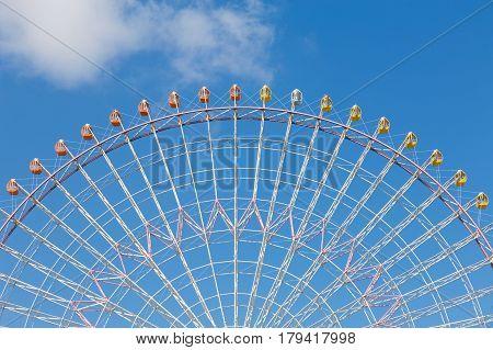 Path of big funfair ferris wheel against blue sky background