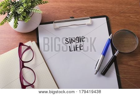 Single Life Word On Paper With Glass Ballpen And Green Plant.