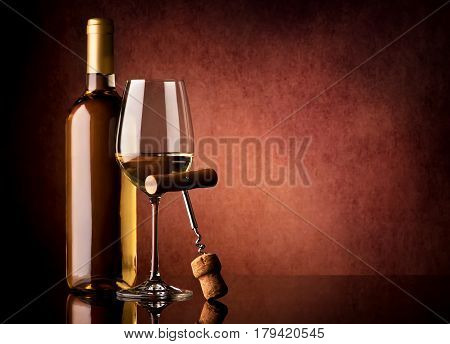 White wine and corkscrew on a vinous background