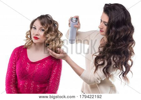 Hairdresser with hairspray and client woman on white background