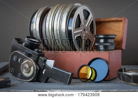 Reels with films in a wooden box lens color filters and an old movie camera are on the table