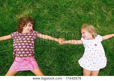 two sister girls lying on meadow green grass like friends playing