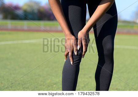 Sporty Muscular Young Woman Clutching Her Knee