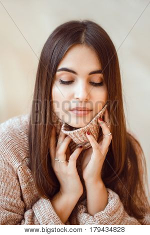 Closeup portrait of pensive white Caucasian European brunette young beautiful woman model with long dark red hair and brown eyes in turtleneck sweater looking down