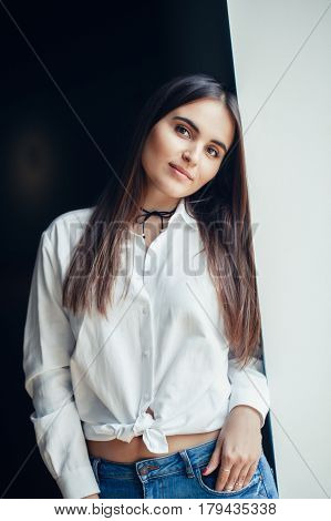 Portrait of smiling white Caucasian brunette young beautiful girl woman model with long dark hair and brown eyes in white shirt tied in a knot looking in camera on black background