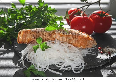 cellophane with pieces of roasted salmon with tomatoes onion and parsley