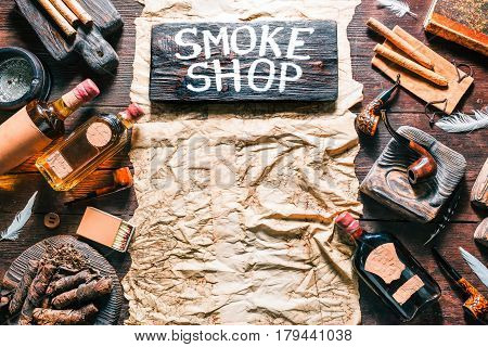 Background of old paper on dark wood desk. Frame of smoking pipes, cigars, tobacco and brandy bottles. Western style. Wooden signboard with text 'Smoke shop'. Top view