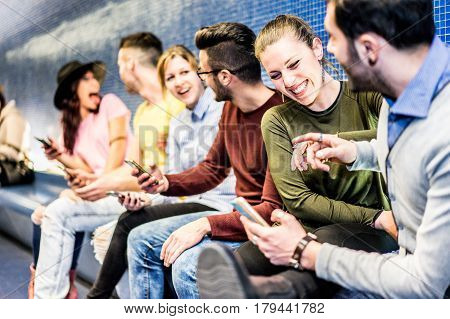 Group of happy friends having fun with mobile smartphones inside underground metro subway - Young people laughing together waiting for tube train - Focus on right girl face